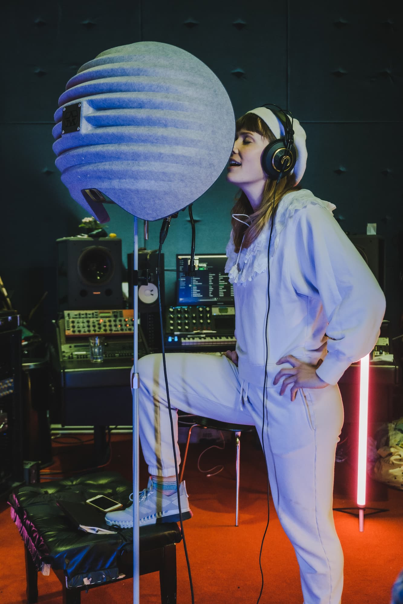Oh Land singing into a microphone in her record studio.