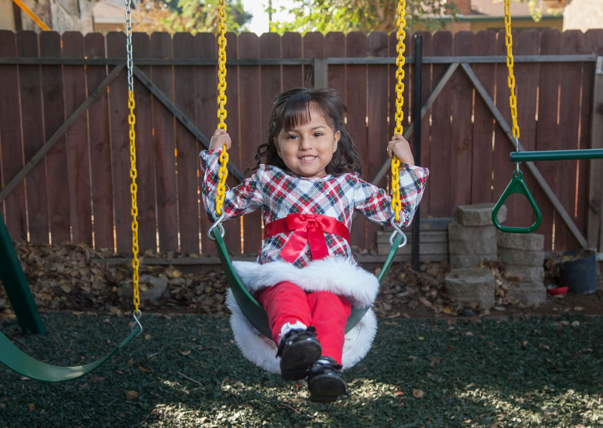 Brown-haired girl in a checkered dress and red pants sitting on a swing in front of a wooden fence