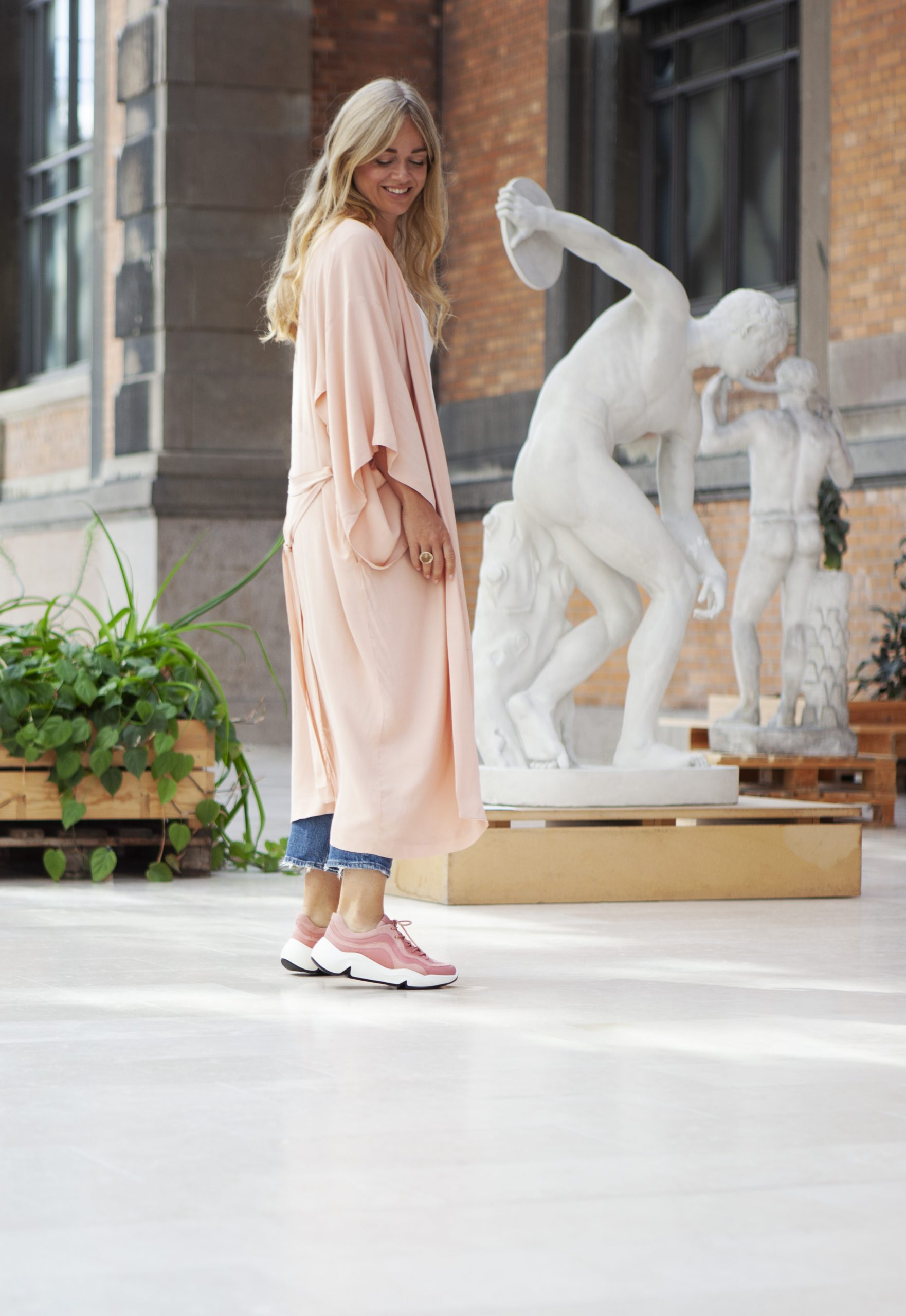 Ebba von Sydow wearing a light pink robe standing outside in front of an art museum with white antique statues