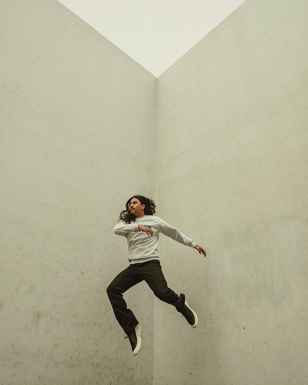 Denny Balmaceda jumping high in the air in the corner of a concrete wallsection