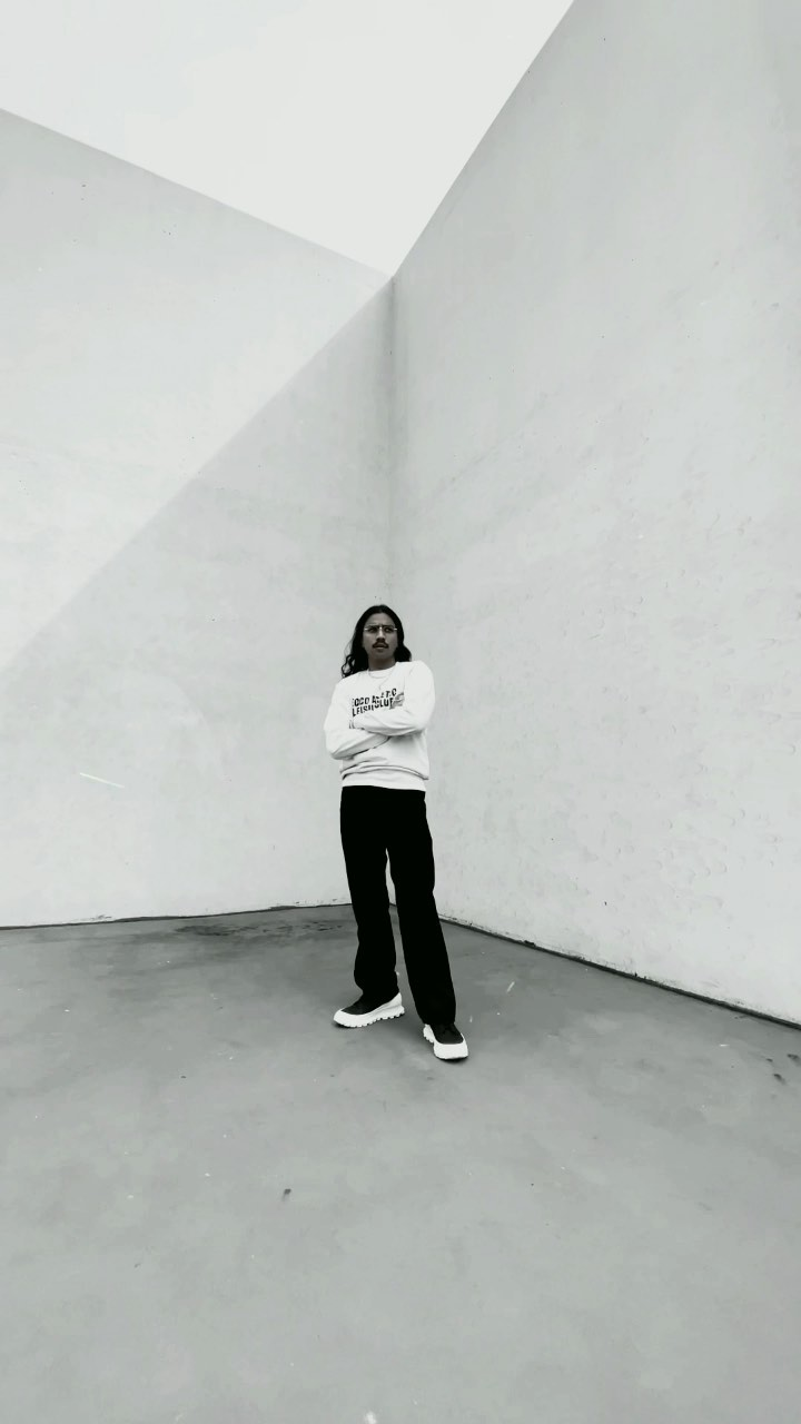 Denny Balmaceda standing in a corner of a concrete building wearing a white sweatshirt and black pants