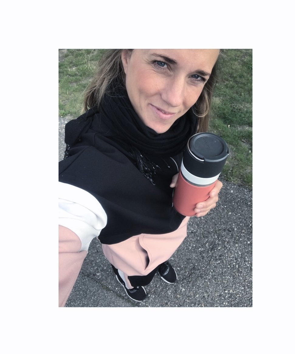 A woman taking a walk with a cup of coffee
