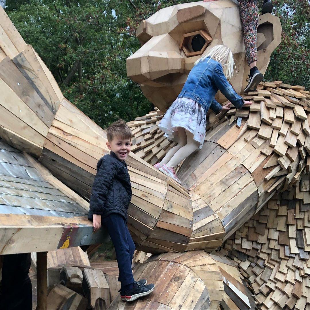 A kid climbing on a wooden troll