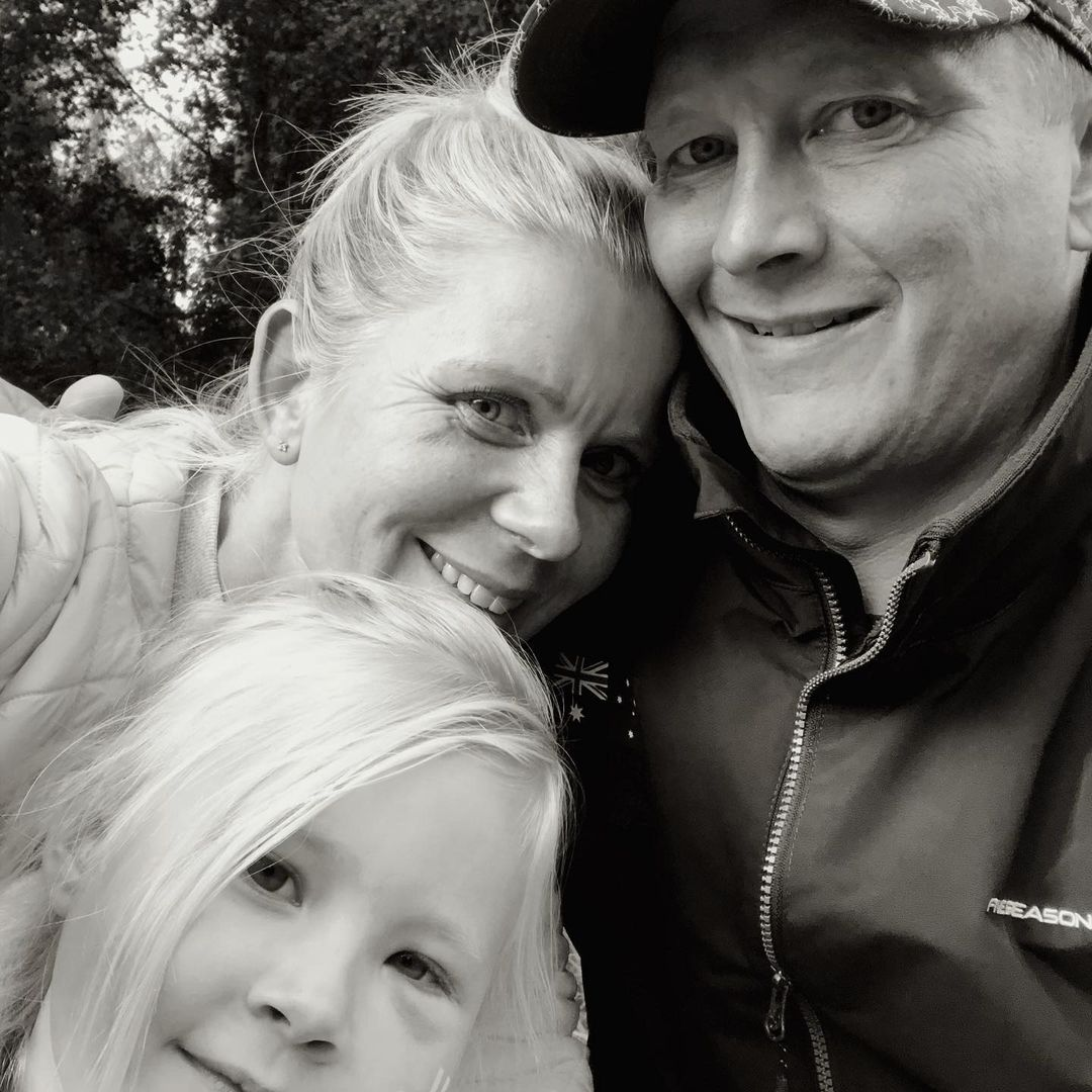 A family of 3 in a black and white selfie
