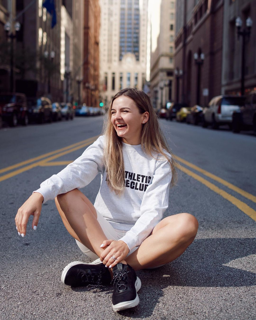 Olia sitting in the middle of the street surrounded by tall buildings